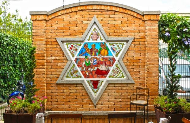A Estrela de Davi decorada com símbolos que falam do trabalho na lavoura, colheita, tratamento e nobreza do produto.