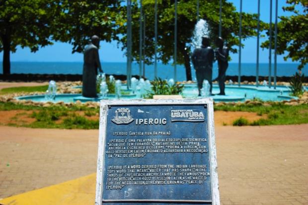 Placa na praia de Iperoig e conjunto de estátuas que contam a história da fundação de Ubatuba