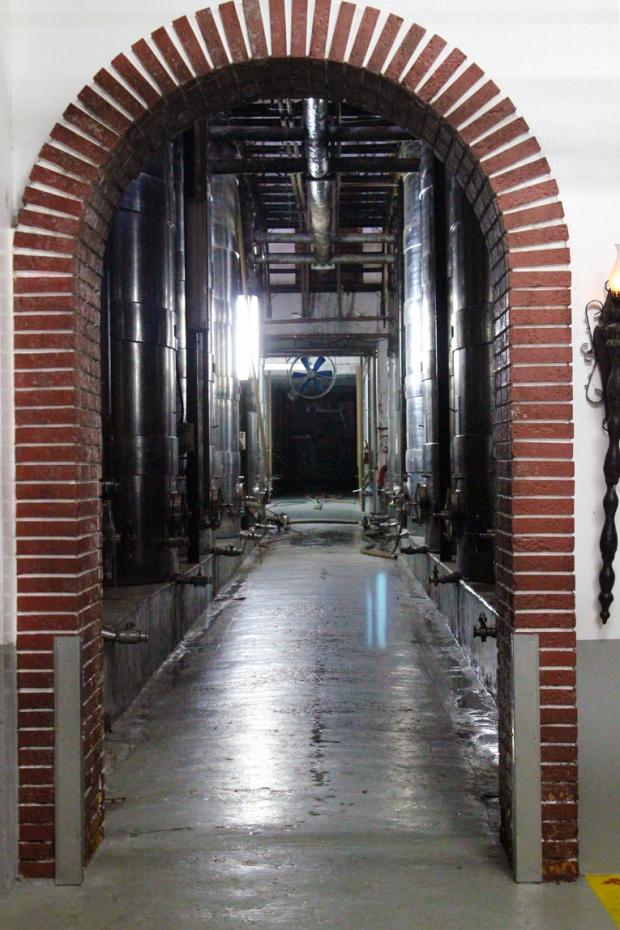 A passagem por debaixo da rua. Há muitas passagens chamativas na fábrica. Uma delas está decorada de garrafas de vinhos premiados.