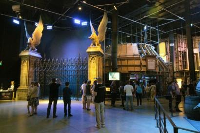Passe pelo grande portão de Hogwarts.
