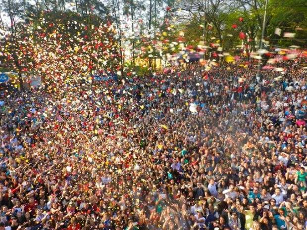 Pessoas felizes e cantando enquanto as pétalas vão caindo e colorindo a vida.