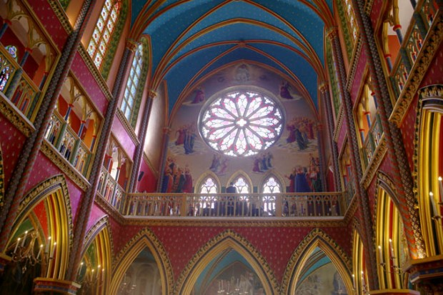 O balcão dos músicos e o vitral de mandala, comum na arquitetura gótica.