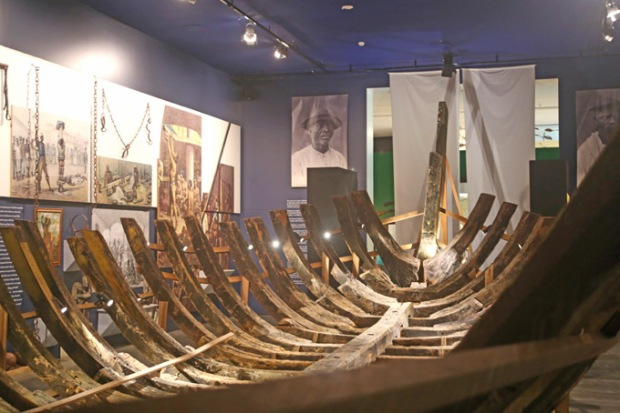 A armação de um navio negreiro. Ao redor, desenhos, pinturas e material histórico sobre o tráfico de escravos.